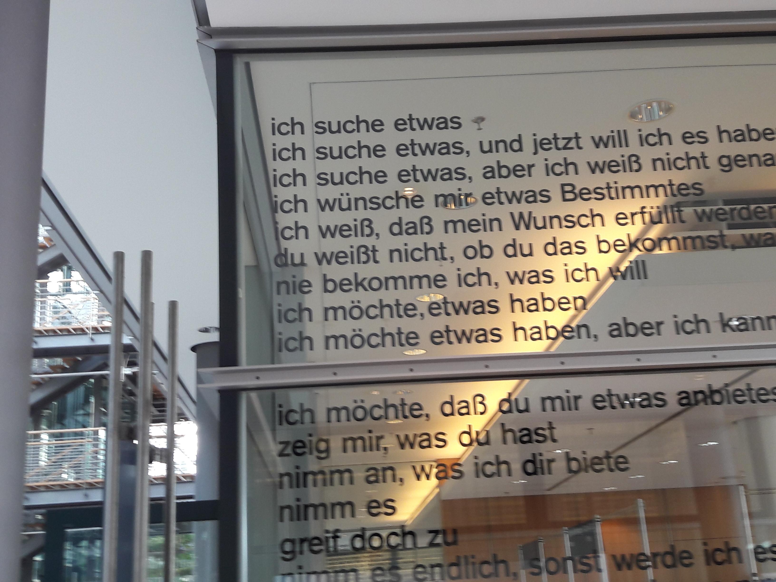 Gedicht an der Glaswand des Pressezentrums.
