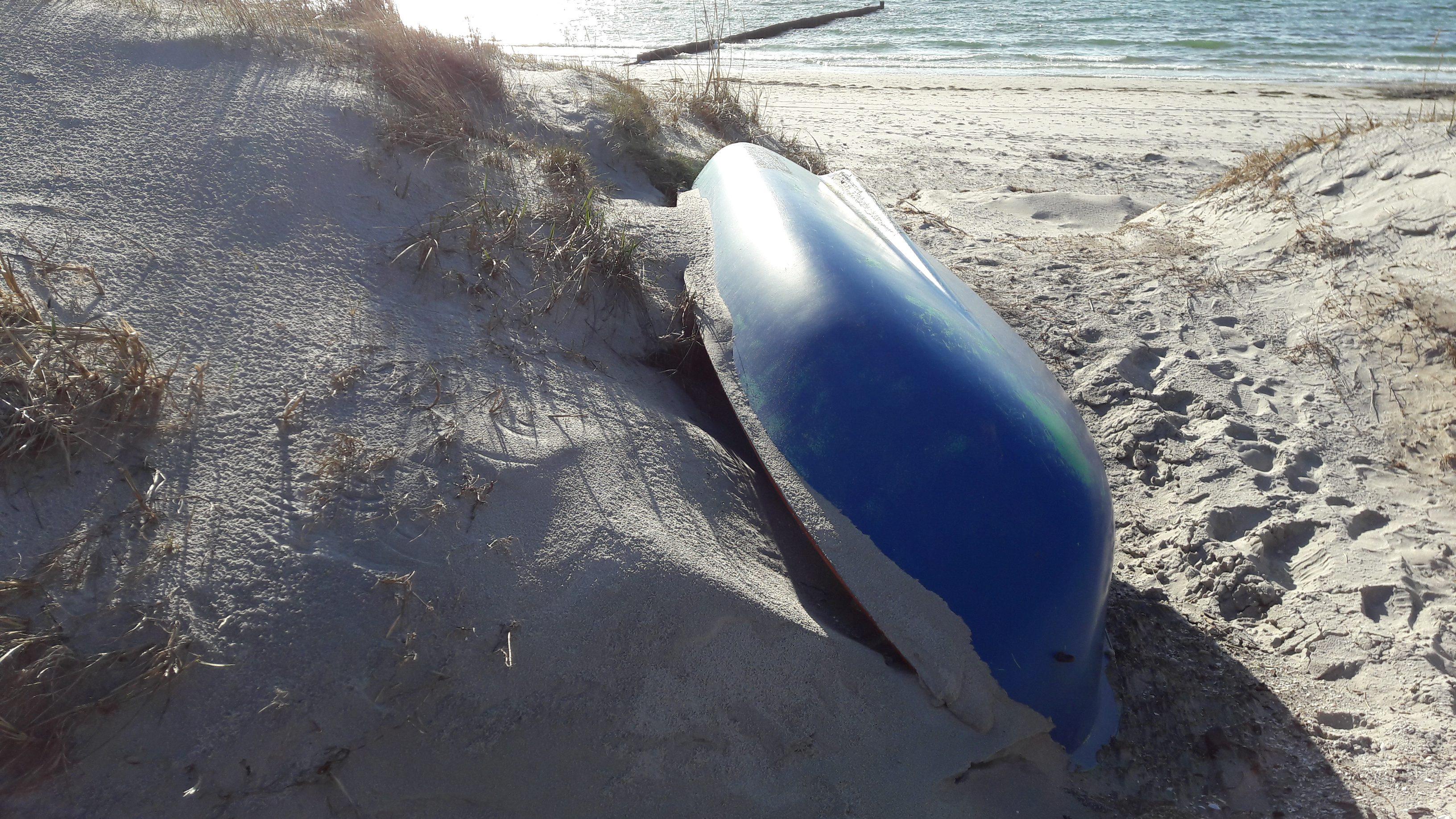 Ein blaues Ruderboot liegt am Strand